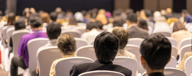 Banner cover page of rear view of audience listening speakers on the stage in the conference hall or seminar meeting, business and education about investment Premium Photo