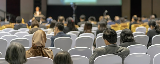 Banner cover page of rear view of audience listening speakers on the stage in the conference hall Premium Photo