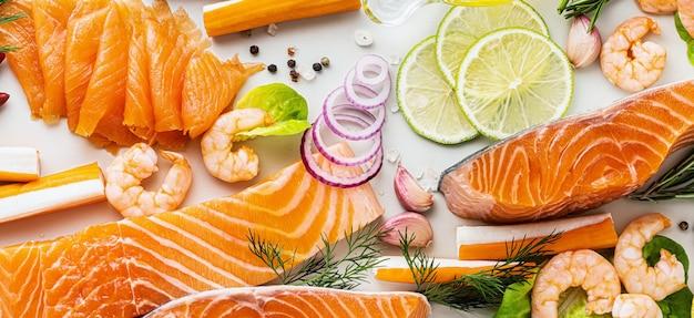 スパイス、野菜、オリーブオイルのテーブルに新鮮な魚介類のバナー:スーパーや魚の寿司レストランの新鮮なスモークサーモン、エビ、カニの棒。 Premium写真