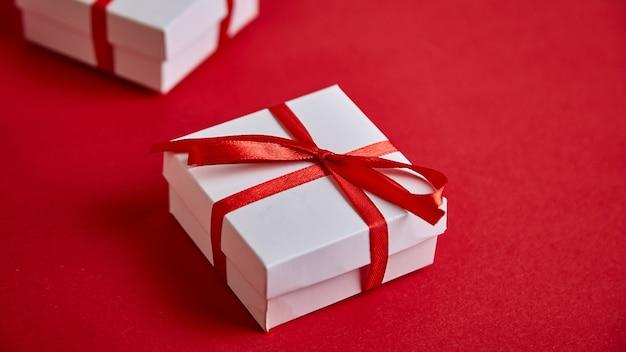 赤い背景の赤いリボンと豪華な白いギフトボックスのバナー。 Premium写真