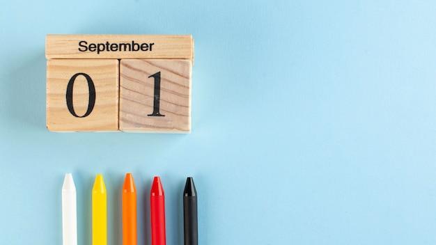 Баннер с деревянным календарем 1 сентября, цветные ручки на синем фоне. скопируйте пространство. начало учебного года Premium Фотографии
