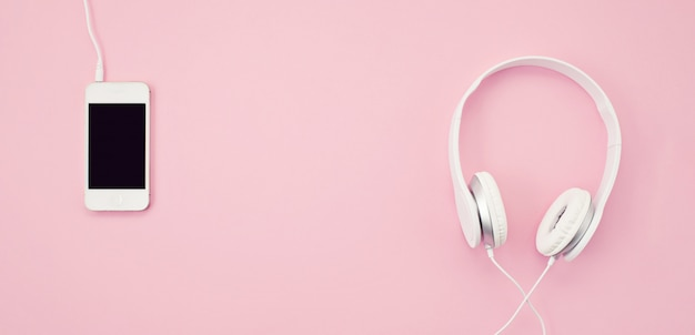 Banner with the cell phone and headphones over the pink background. music, entertainement, online playlists Premium Photo