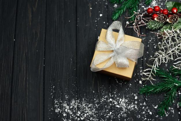 Баннер с подарочной коробкой и елочным украшением для праздника рождества и нового года зимой со снегом на деревянном фоне Premium Фотографии
