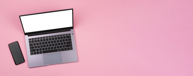 Banner with a smartphone and a white mockup on a laptop screen on a pink background Premium Photo