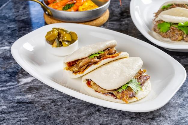 アヒルの切り身とbaoのビューを閉じます。グアバオ、白い皿に蒸しパン。大理石のテーブルで台湾の伝統的な料理gua bao。アジアンサンドイッチ蒸し。アジアのファーストフード。肉 Premium写真