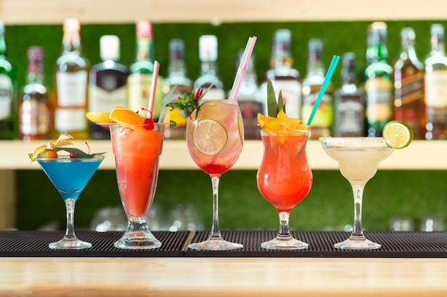 Bar counter cocktails drinks selection multicolored summer drinks Premium Photo