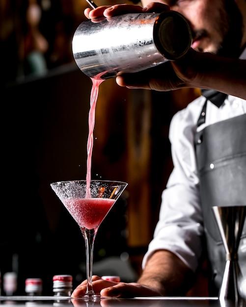 Il barista versa il cocktail dallo shaker al bicchiere da martini Foto Gratuite