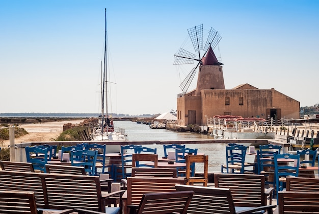 Bar with view of mozia salt flats and an old windmill in marsala, sicily Premium Photo
