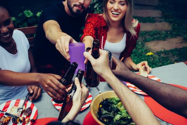 Барбекю и вечеринка. счастливая группа друзей с барбекю на природе Premium Фотографии