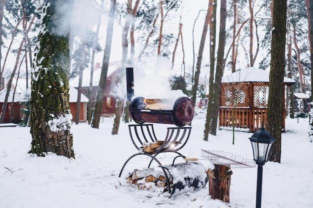 Barbecue grill in the snow-covered complex in smoke Premium Photo