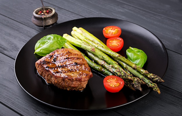 Barbecue grilled beef steak meat with asparagus and tomato. Premium Photo