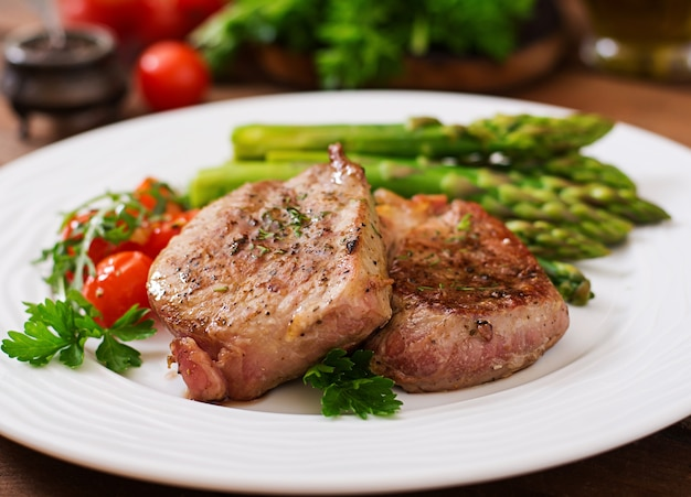 Barbecue grilled beef steak meat with asparagus and tomatoes. Free Photo