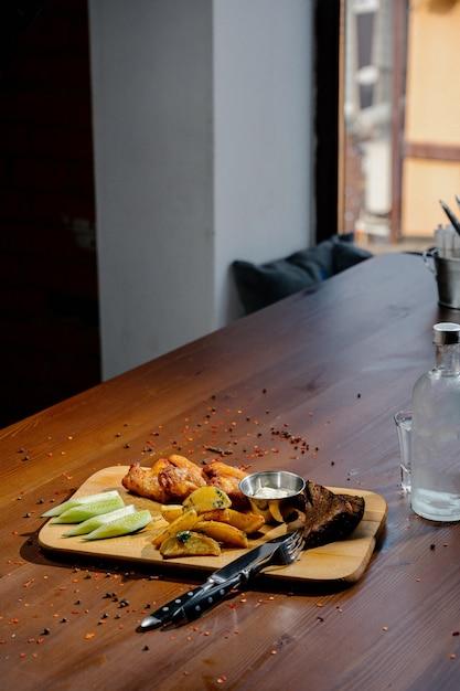 バーベキュー手羽先のグリルは、フライドポテト、木の板に醤油をクローズアップ。肉料理のコンセプトです。フライドチキンとフライドポテト Premium写真