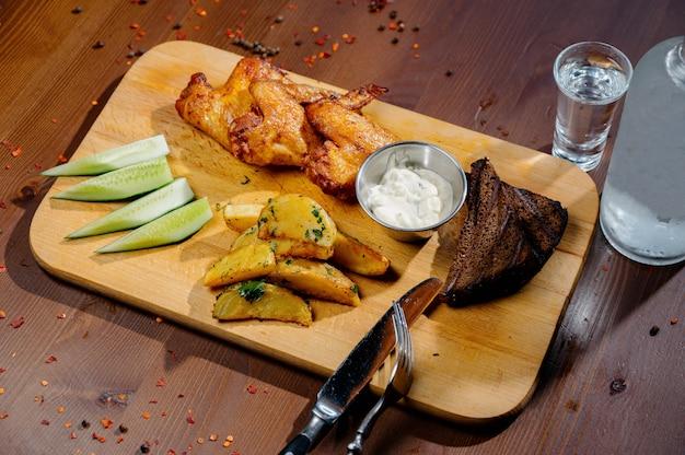 バーベキューグリル手羽先は、フライドポテト、ダークテーブルの上の木の板のソースでクローズアップ。肉料理のコンセプトです。フライドチキンとフライドポテト Premium写真