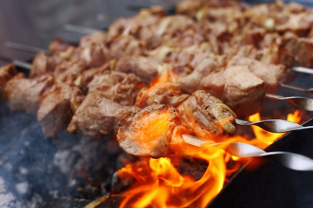 Barbecue in nature in summer. pork meat in the smoke on the coals, healthy food, closeup. Premium Photo