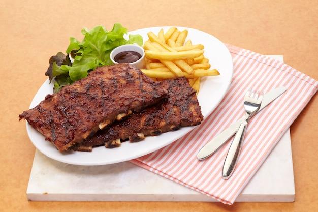Свиные ребрышки барбекю подаются с жареной по-французски и салатом Premium Фотографии