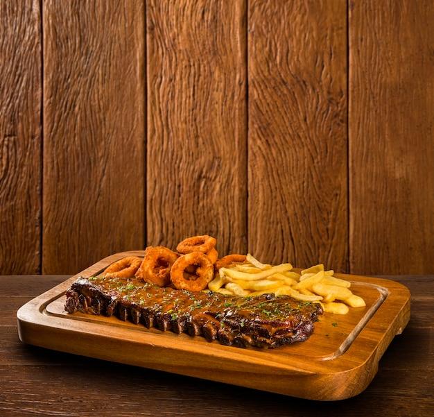Свиные ребрышки барбекю с картофелем фри и луковыми кольцами. Premium Фотографии