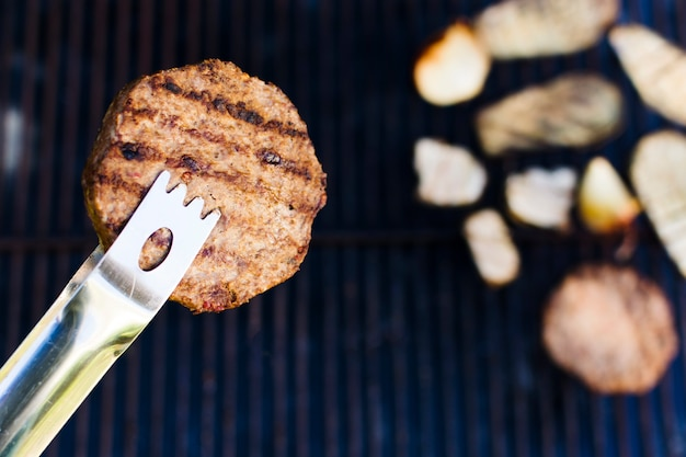 Barbecued meat cutlet in forceps during picnic Free Photo