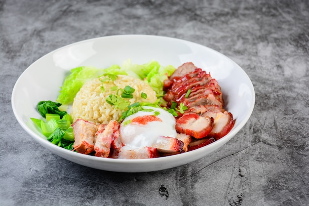 Barbecued red pork and crispy pork in red sauce, served with rice and vegetable on white plate, Premium Photo