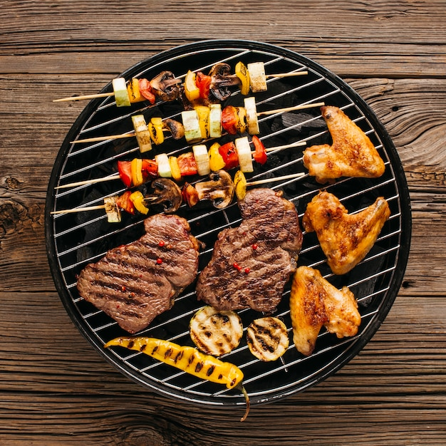 Barbecuing assortment of meat with sausages and vegetable Free Photo