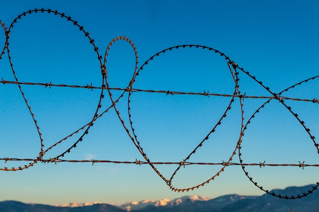 Barbed wire fence against the blue sky and mountains. restraint, private property Premium Photo