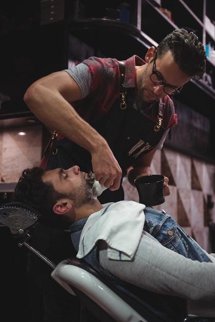 Парикмахерская, применяя крем на бороде клиентов Бесплатные Фотографии