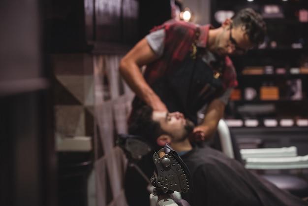 クライアントのあごひげにクリームを塗る床屋 無料写真