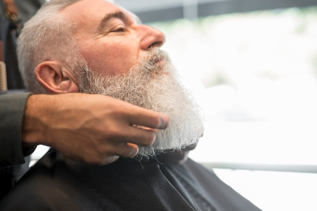 Barber correcting beard to aged client Free Photo