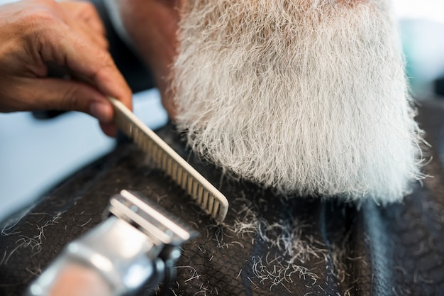 Barber cutting beard to client in salon Free Photo