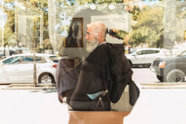 Barber cutting haircut bearded elderly client Free Photo
