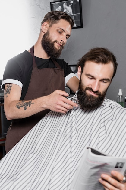Barber cutting male customer's beard with scissors Photo ...