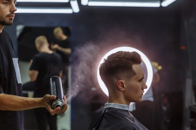 Barber makes hair styling with hair spray after haircut at the barber shop. Premium Photo