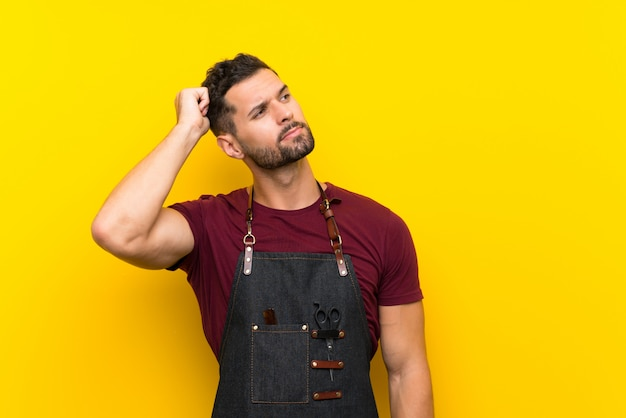 Barber man in an apron having doubts and with confuse face expression Premium Photo