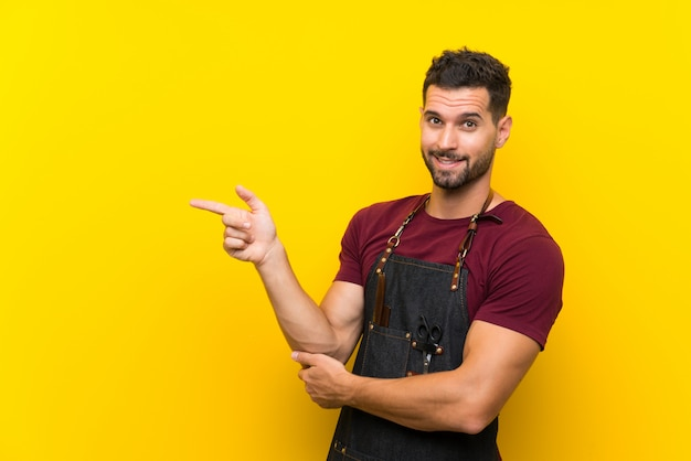 Barber man in an apron pointing finger to the side Premium Photo