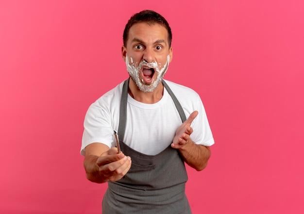 Uomo del barbiere in grembiule con schiuma da barba sul viso che tiene il rasoio guardando in avanti con le braccia fuori come chiedere o discutere in piedi sul muro rosa Foto Gratuite