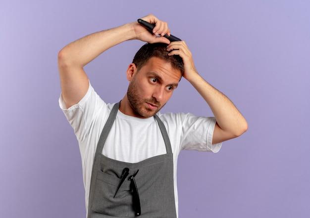 보라색 벽 위에 서 심각한 얼굴로 그의 머리를 빗질 앞치마에 이발사 남자 무료 사진