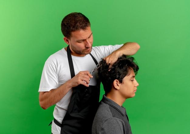 녹색 벽 3 위에 서 만족 클라이언트의 가위로 앞치마 절단 머리에 이발사 남자 무료 사진