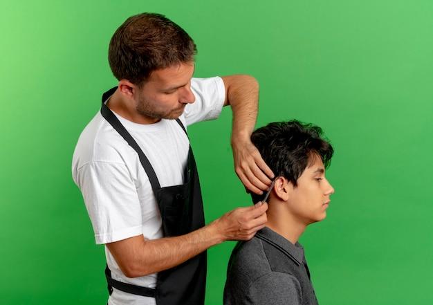 녹색 벽 위에 서 만족 클라이언트의 가위로 앞치마 절단 머리에 이발사 남자 무료 사진