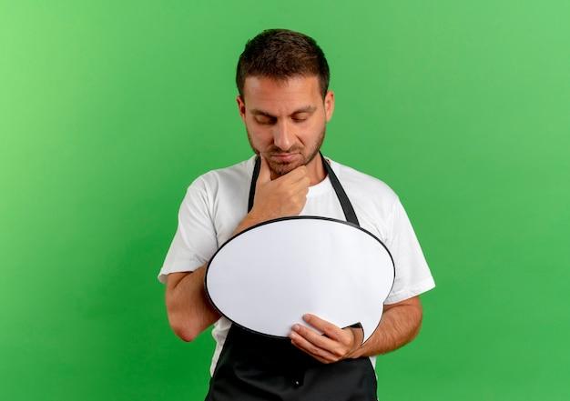 녹색 벽 위에 서 생각 잠겨있는 식으로 찾고 빈 연설 거품 기호를 들고 앞치마에 이발사 남자 무료 사진