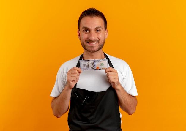 오렌지 벽 위에 서있는 얼굴에 미소로 정면을 찾고 현금을 들고 앞치마에 이발사 남자 무료 사진