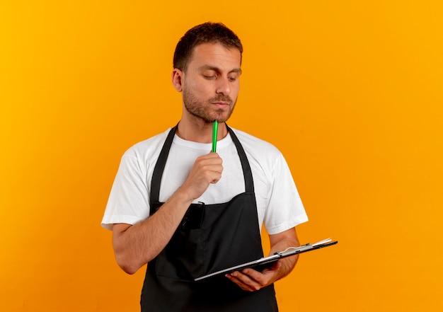 클립 보드와 펜을 들고 앞치마에 이발사 남자가 오렌지 벽 위에 서있는 잠겨있는 표정으로 찾고 무료 사진