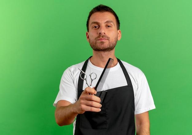 빗과 가위를 들고 앞치마에 이발사 남자가 녹색 벽 위에 서있는 자신감있는 표정으로 앞을 찾고 무료 사진