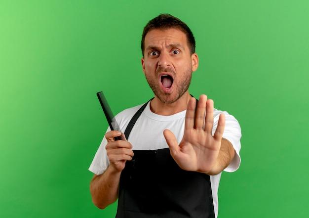 녹색 벽 위에 서 외치는 손으로 정지 신호를 만드는 빗을 들고 앞치마에 이발사 남자 무료 사진