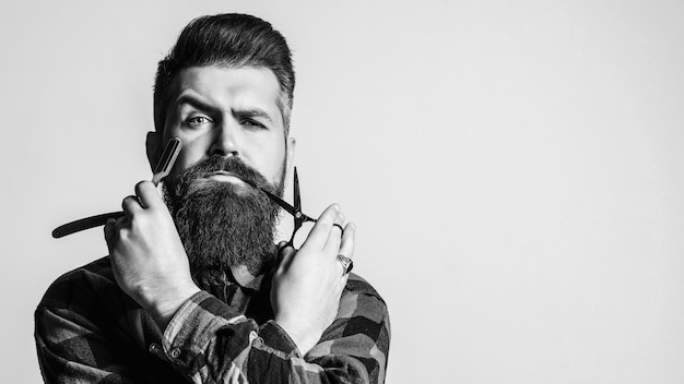Barber man with straight razor and scissors. Premium Photo