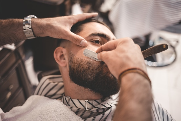 Barber shaves the beard of the client Premium Photo