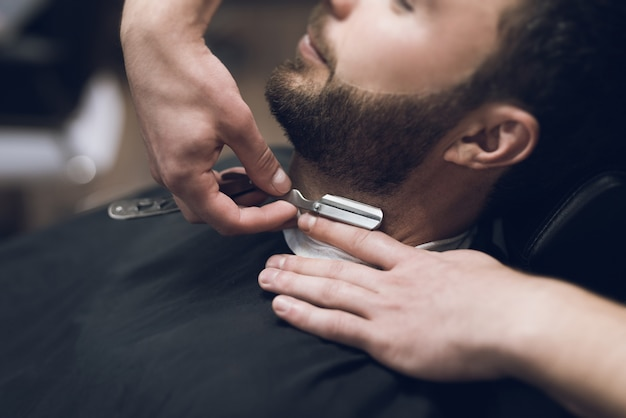 Barber shaves his head, mustache and beard to man Premium Photo