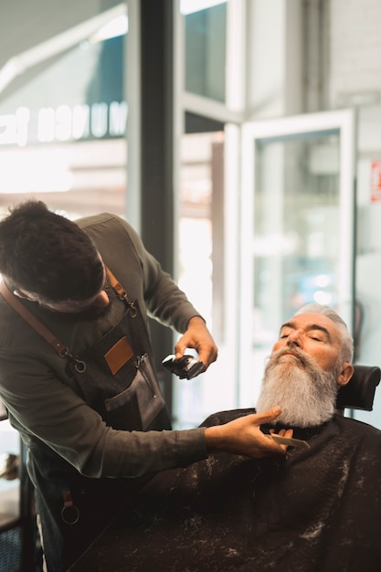 Barber shaving beard to elderly man Free Photo