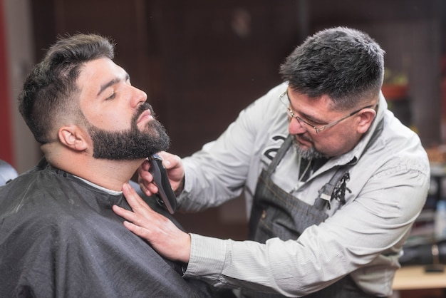 Barber shaving the beard of a handsome bearded man with an electric razor at the barber shop. Premium Photo