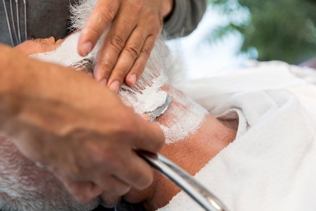 Barber shaving beard to man in salon Free Photo