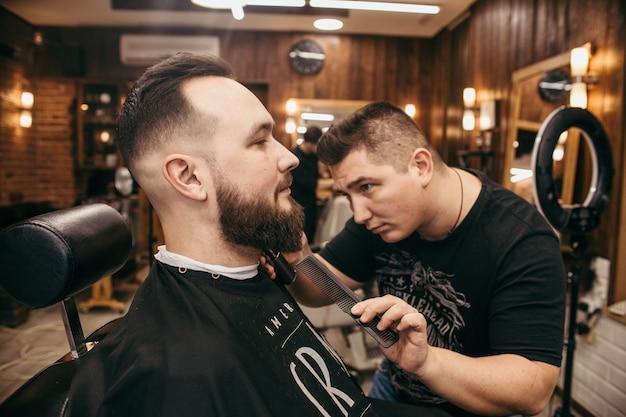 Парикмахерская, мужчина с бородой, парикмахерская. профессиональная стрижка, ретро прическа и укладка. красивые волосы и уход, парикмахерская для мужчин. обслуживание клиентов. Premium Фотографии